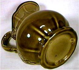 Green-brown Metlox pitcher with three flaws from firing pins on foot.