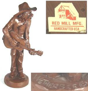 "Red porcelain man with a guitar and wide-brimmed hat from Red Mill Mfg., marked ""Wetherbee""."
