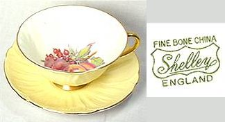 "Pale yellow cup and saucer with fruit painted inside cup. Mark reads ""Fine Bone China, Shelley, England""."