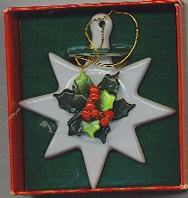White eight-pointed star porcelain ornament with holly berries in center.
