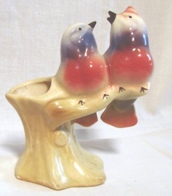 Pair of white songbirds with red bellies and blue throats singing on a yellow stump by American Bisque.