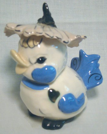 Fat cream colored bird with blue highlights and a flower hat by Kay Finch.