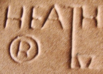 Heath Ceramics mark in capital letters on brown pottery surface.