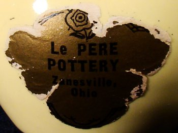 Partial LePere Pottery sticker on a yellow miniature pitcher.