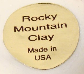 Round Rocky Mountain Clay Made in USA label on red swirl clay dish.