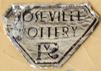 Roseville Pottery foil label with RV logo on yellow clay Baneda from 1933.